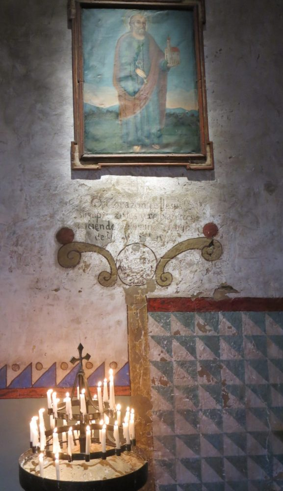 painted wall in Carmel mission: Above is either a painting or a mural with a frame: it depects a saint in robes holding a small model of the mission building. Below are some words, very faded, and below that a decorative border in blues, reds and browns. A round tray holds a round candle holder with many small candles burning in it at bottom left.