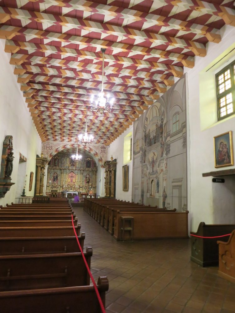 view of the interior of Mission Dolores with painted ceiling: a long narrow room, looking toward the altar in the distance, which appears to have a number of figures painted on its back wall.  An aisle down the center of the room with pews on either side. The ceiling has heavy beams going across and they and the spaces between them are painted with a simple geometrical pattern of rectangles and triangles in dark red, white, grey and mustard yellow. ON the right-hand wall is a large mural, but it's hard to see what it depicts from this angle.