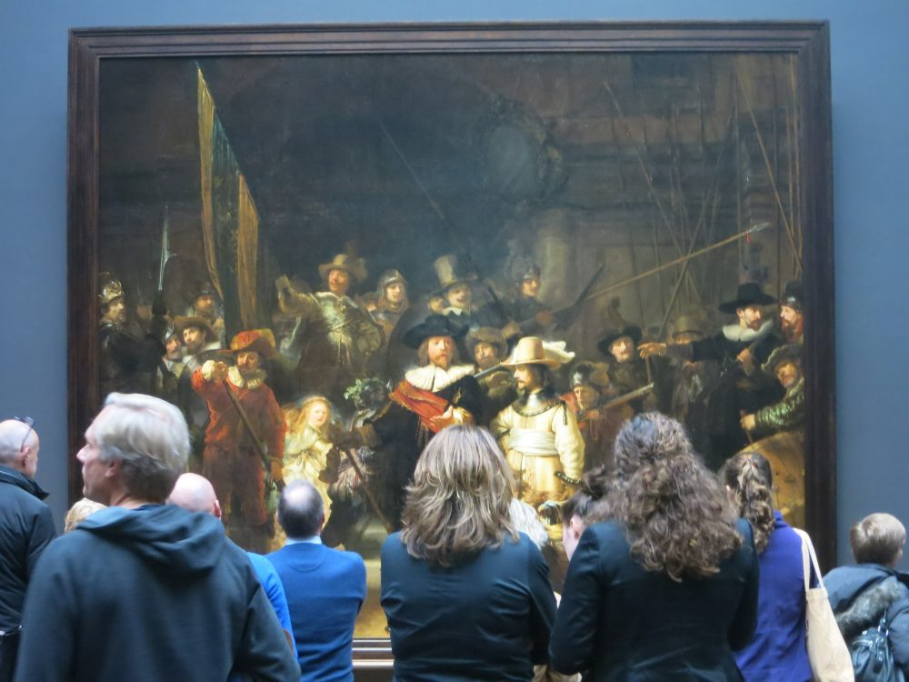 The Night Watch is a large painting of a group of men in the 16th century. In front of the painting, a group of people, backs to the camera, obscure the bottom half of the painting. They are all coincidentally wearing blue jackets, and the wall around the painting is also blue.