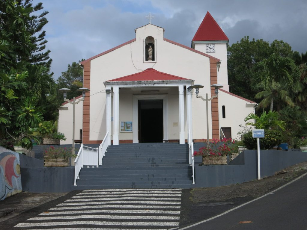 Seen from the front: stairs up to the entrance, which has a roof held by four columns, two on each side. Above the entrance, a statue niche iwth a statue inside of Mary with the infant Jesus. The tower is behind the church and slightly to the right; it is attached to the back right corner of the church.