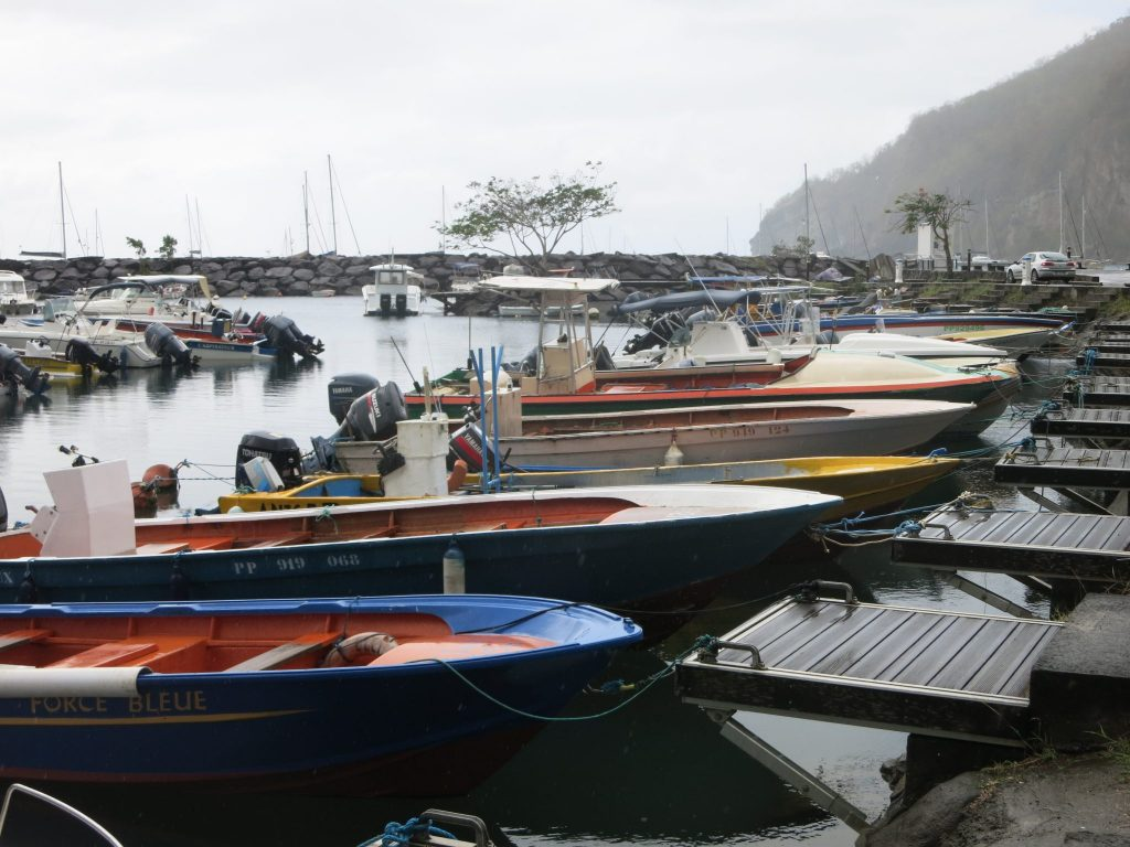 A row of small open top boats with outboard motors. The nearest one is blue and the others are a range of colors. Each has a small dock. In the background is a stone jetty.