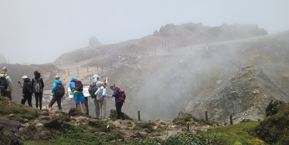 a group of hikers, seen from behind, stand in a row looking at a hole that is partly visible behind them. White smoke is visible rising from the hole.