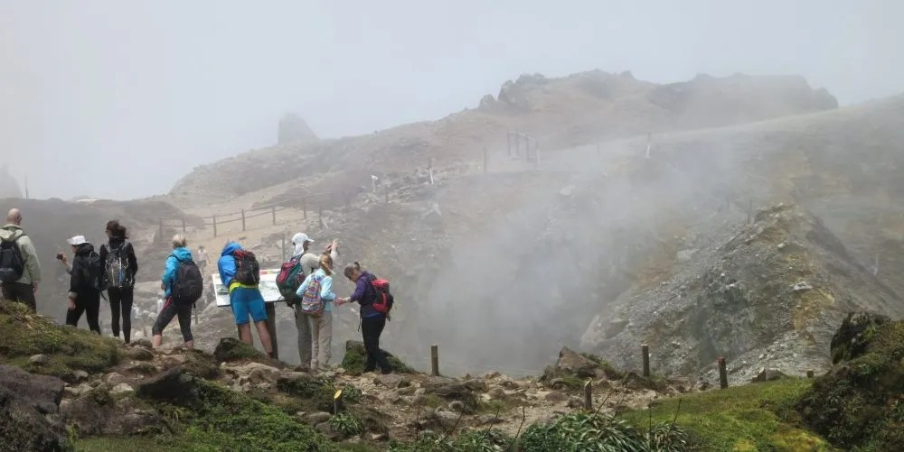 a group of hikers peer into the crater of La Soufrière volcano