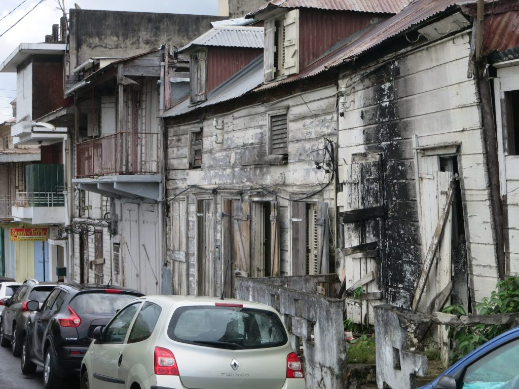 view of a row of wooden houses in Guadeloupe, in very bad condition, looking like there might have been a fire.