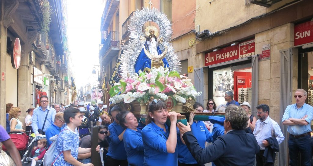 In old Barcelona, the women carry the Mary figure on their shoulders in Barcelona. The figure is decorared with a crown and surrounded by flowers.