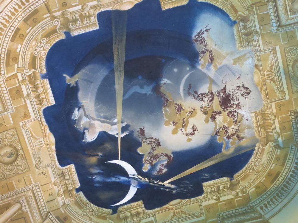 The ceiling of the throne room in the Gala Dali castle references rococo style, but with a surrealistic twist.