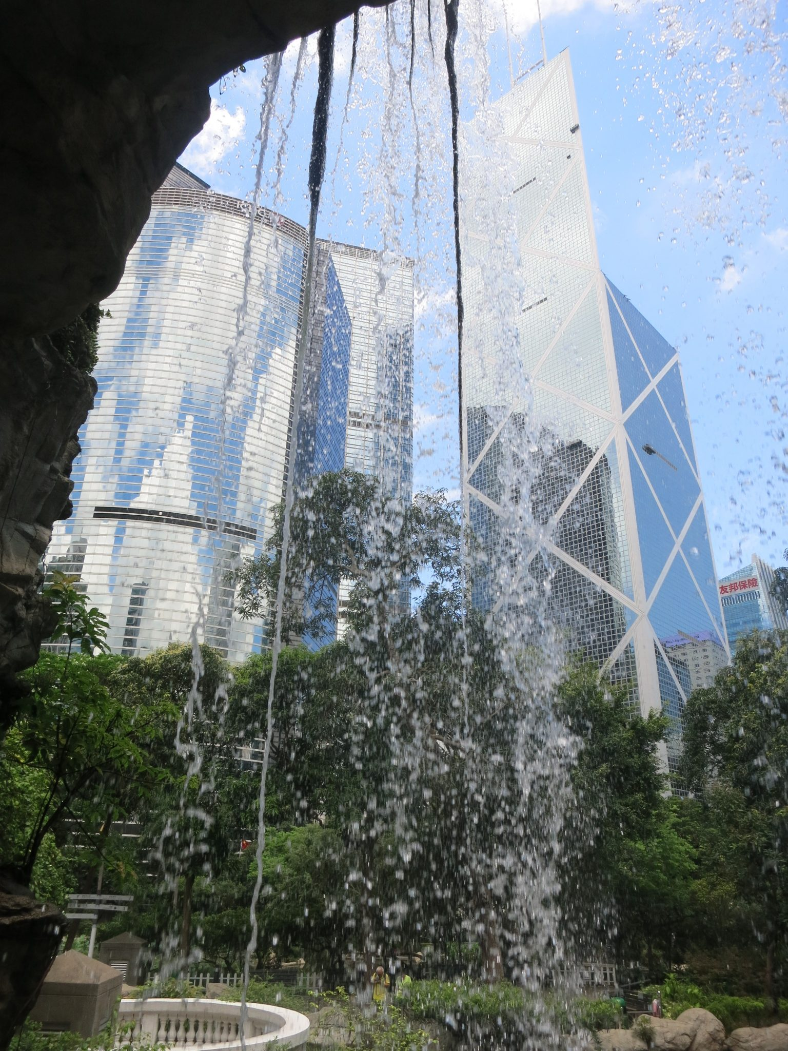 Some Hong Kong Buildings As Seen Through A Landscaped Waterfall In Hong Kong Park