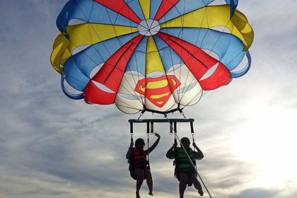 two people strapped under a parachute, parasailing