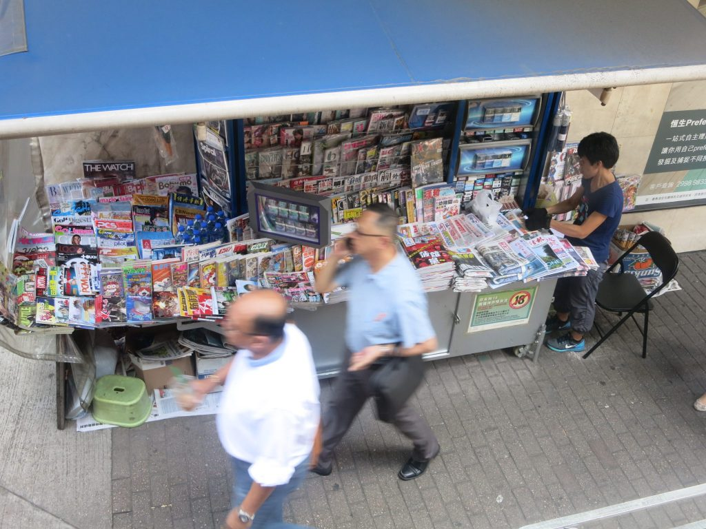 view down from a bus window, shows a newsstand in Hong Kong, with a woman working there, and pedestrians passing. The newstand is covered with lots of magazines and newspapers and has a blue awning above it.