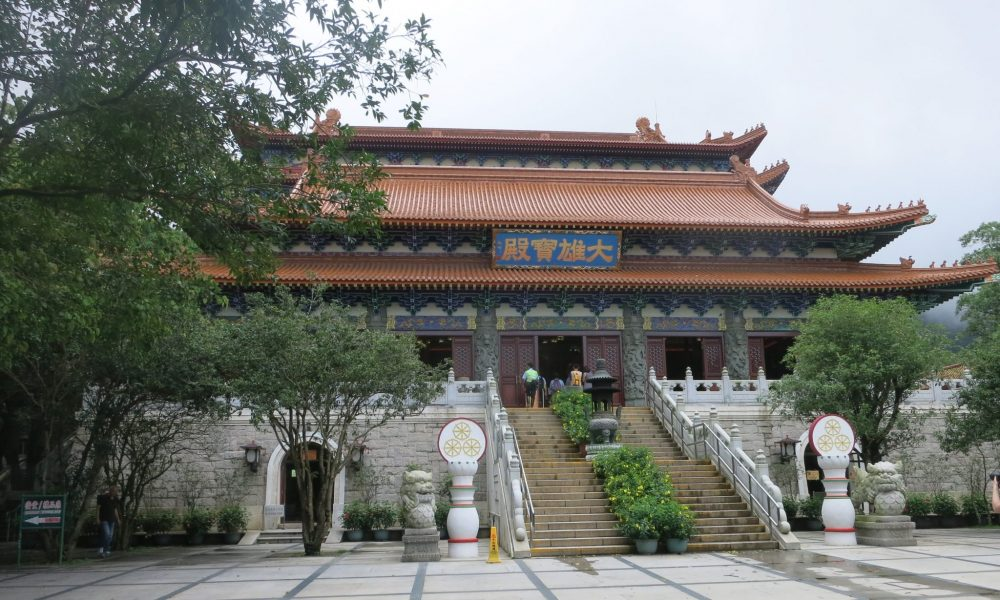 Decorated in a traditional Chinese style, the Po Lin monastery temple contains three Buddha statues. A large stairway leads up to its center. The roof is red and curves in the traditional Chinese style.
