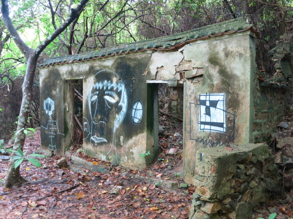 a crumbling house, with graffiti, on Lamma Island
