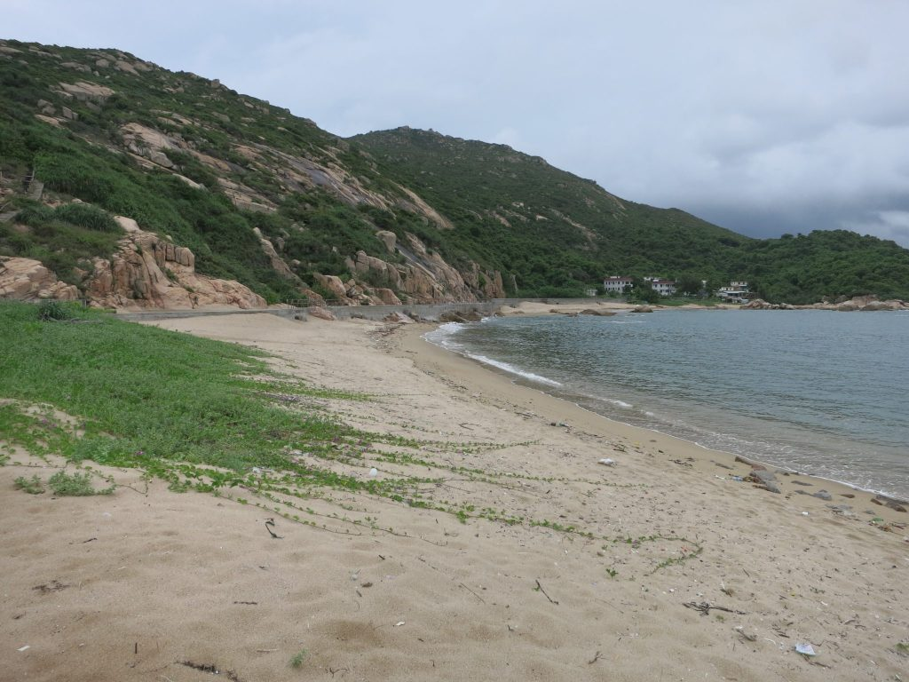 a stretch of empty beach, with a small cluster of buildings visible in the distance, on Lamma Island