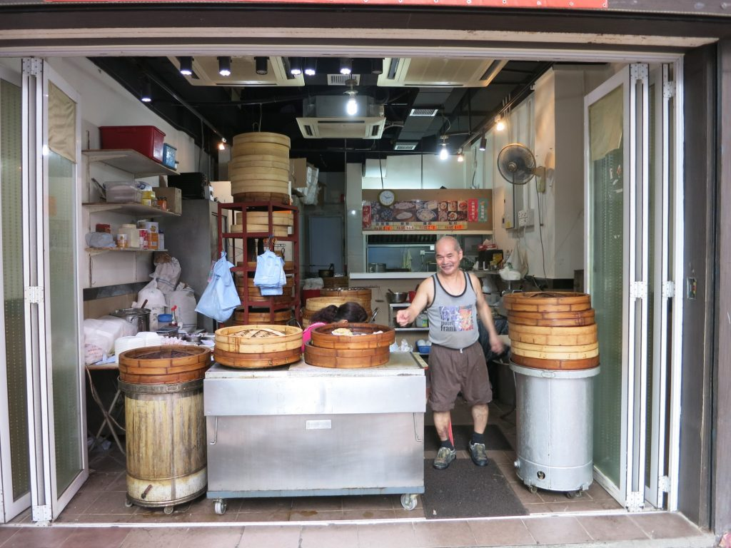 storefront, open to the street in Hong Kong, with large steam baskets holding a variety of dim sum. The owner stands next to where the steam baskets are displayed and smiles for the camera.