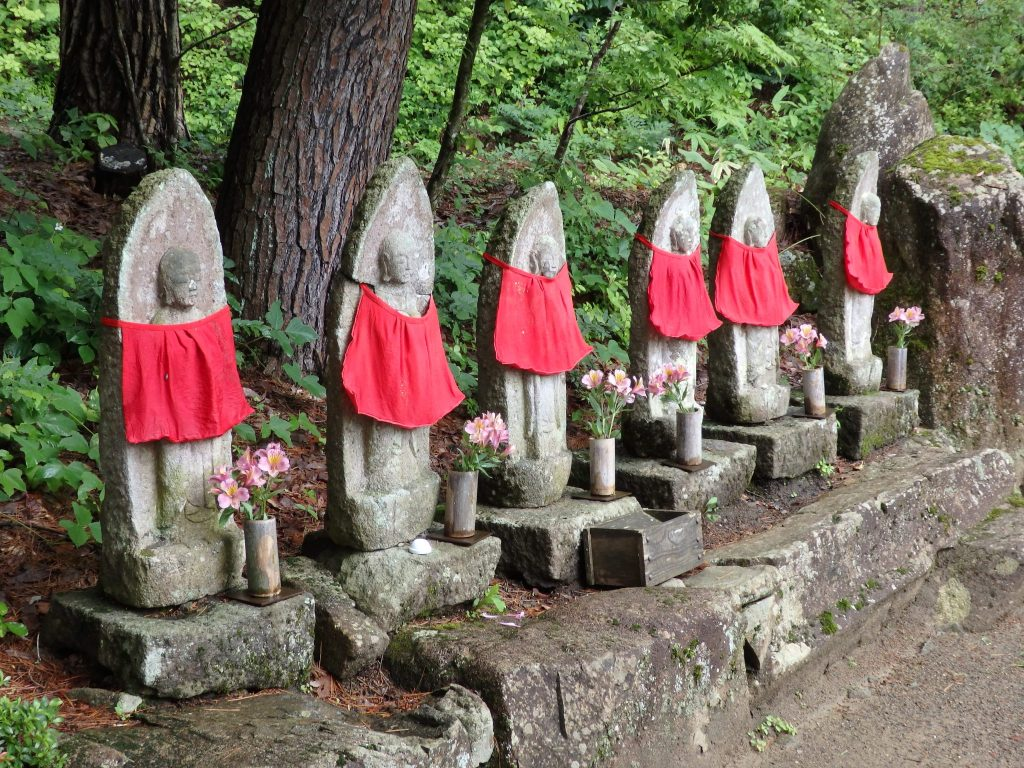 a row of six stone statues, each wearing a red cloth as a sort of bib, in the Hida Folk Village in Takayama, Japan