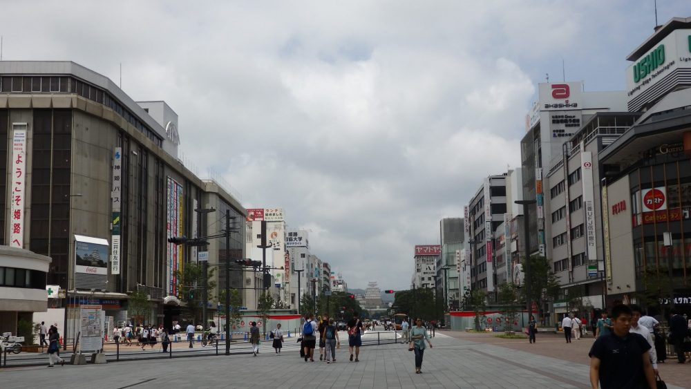 view down a wide street. The castle is visible far in the distance while the street is lined on both sides with unattractive office buildings.