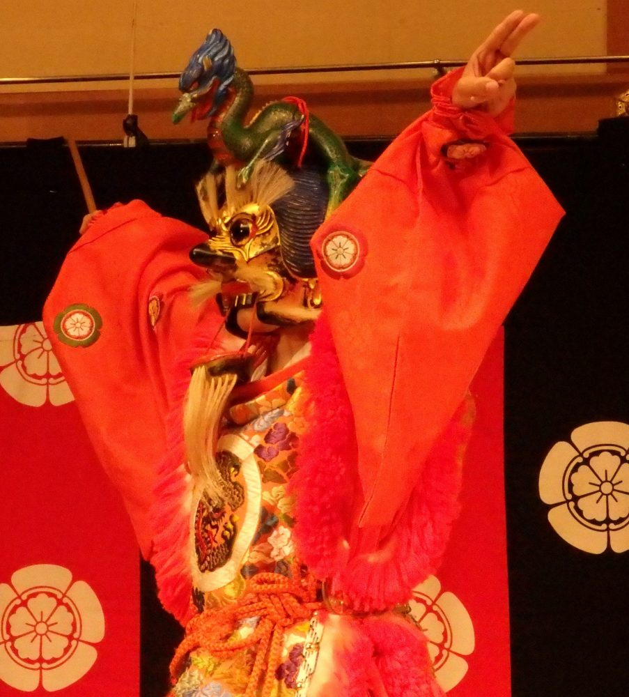 The dancer wears an elaborate, mostly red and gold, costume, and his face is covered with a fierce mask, in Gion Corner