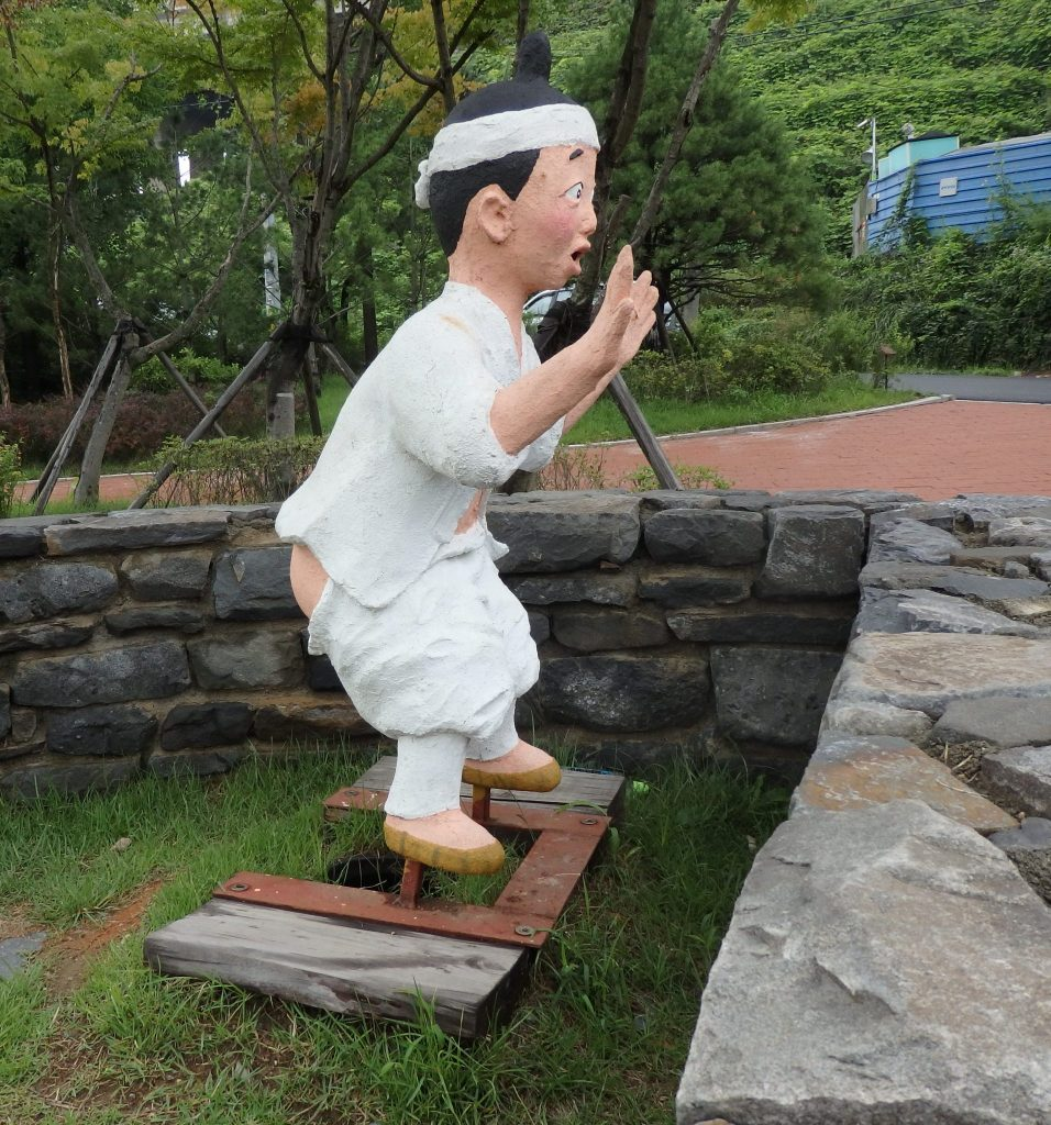 Plaster statue of a Korean peasant squatting, with a surprised look on his face, at the Toilet Museum in Suwon, South Korea