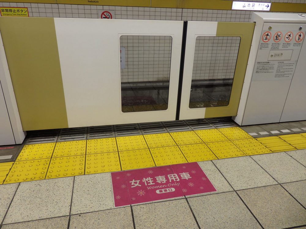 sign on the floor marking a women-only car during rush hour: red sign, printed in Japanese and English