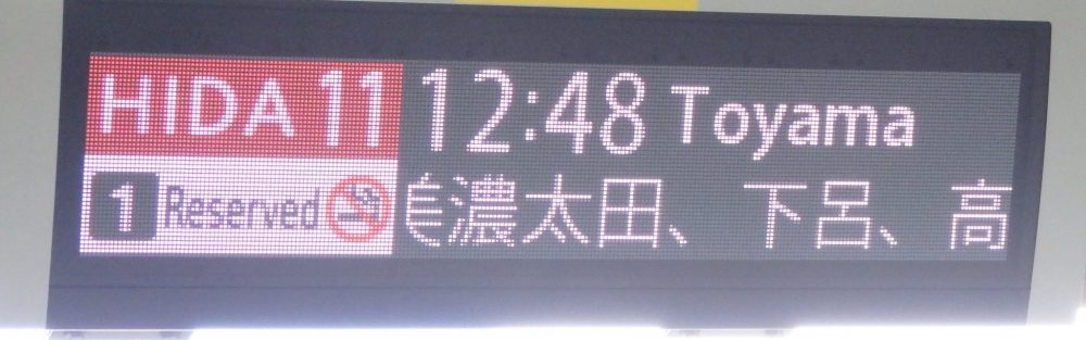 An electronic sign says: Hida 11 train, leaving at 12:48 to Toyama.