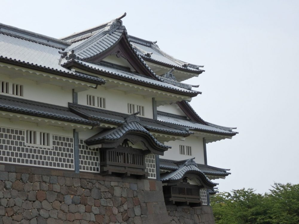 The building is primarily white, with some stone bricks on the ground floor and typical Japanese rooflines that curve. The building stands on a stone wall foundation.
