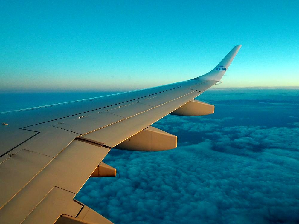 Against a dark blue sunset sky, a view down the wing of an aircraft. KLM logo visible on the wingtip. Below, clouds, looking dark blue because the sun is below the horizon.