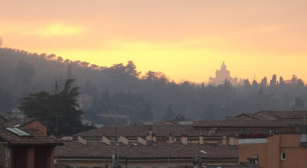 view from the Hotel Touring rooftop terrace at sunset, with the Church of San Luca in the distance.
