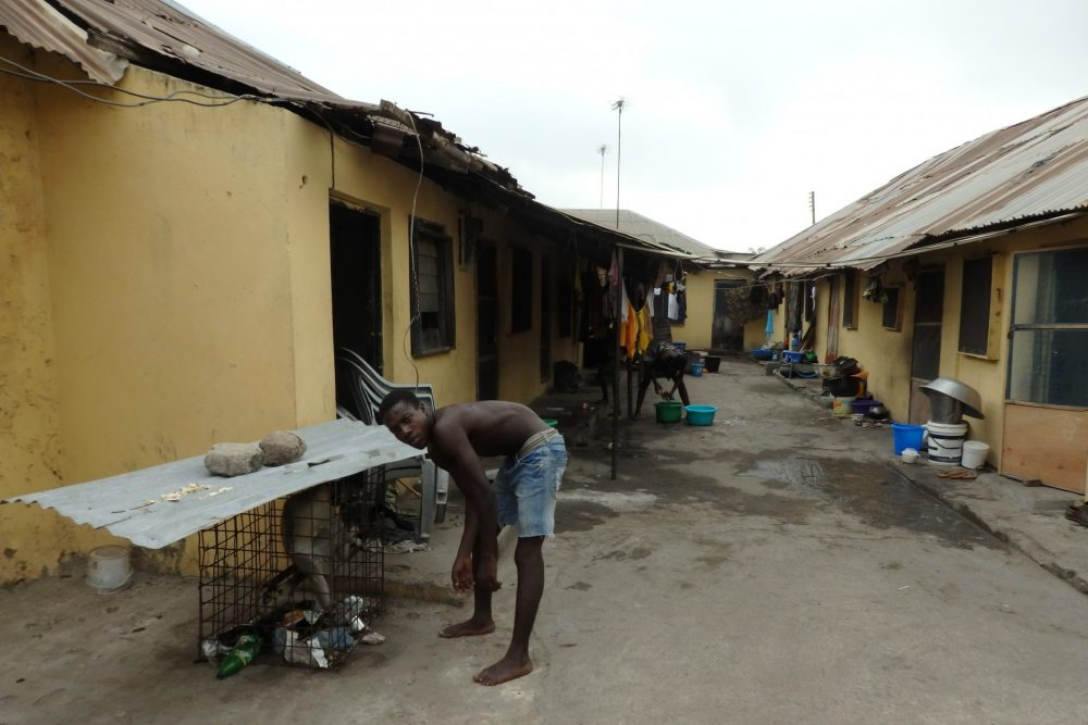 Looking down a dirt alleyway between the former warehouse rows of rooms: single story, with metal roofs. It's clear in the picture that people are living here: pots and pans and buckets sit outside each doorway. In the background a woman is busy cleaning something in a plastic tub on the ground. On the left, in front, a young man in shorts without a shirt leans over to a cage covered in metal sheeting; there's a monkey inside. the young man looks at me, not the monkey.