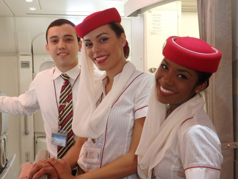 friendly flight attendants on Emirates A380: 3 flight attendants. The one in back is a young man wearing a white shirt and a striped tie in red, white and black. The two in front are women, wearing white shirts with red lines along some of the seams, red beret-shaped hats with whilte scarves hanging from one side of the hat. They all look at the camera and smile.