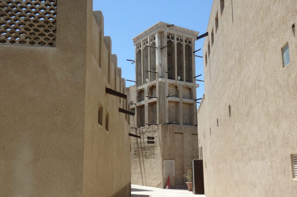 Left and right, sand-colored mud walls, with a few small square windows in flat sides and a few wooden beams protruding here and there. In the center, at the end of the narrow street, is a wind tower. It is a vertical square tower, perhaps 3 or 4 stories tall. Wood beams protrude here and there and the top level looks like it has tall rectangular windows (there are open to the air, chanelling the wind down into the house.)