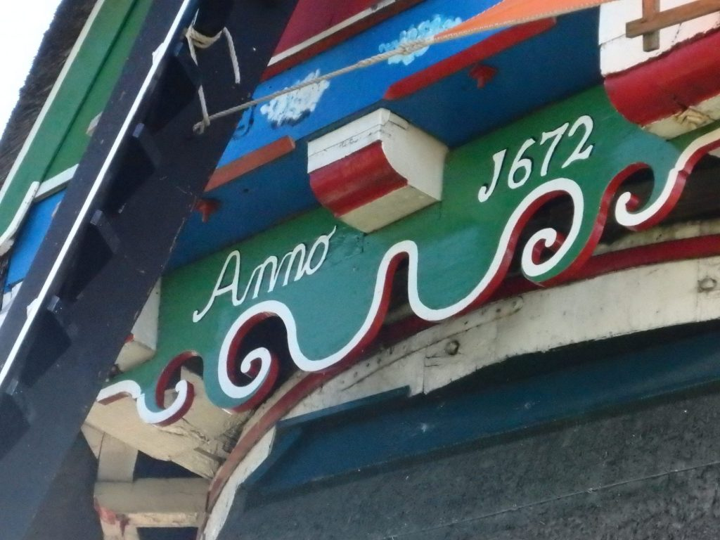 """The woodwork is painted bright green, red, blue and white, with simple curles, like upside down waves, along the edge. The words """"Anno 1672"""" are painted in white on a green background."""
