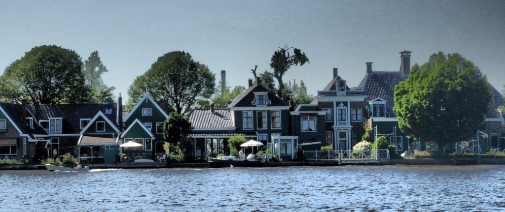 The row of houses sit right on the edge of the water: wooden houses, just 2-3 stories high, with peaked roofs.