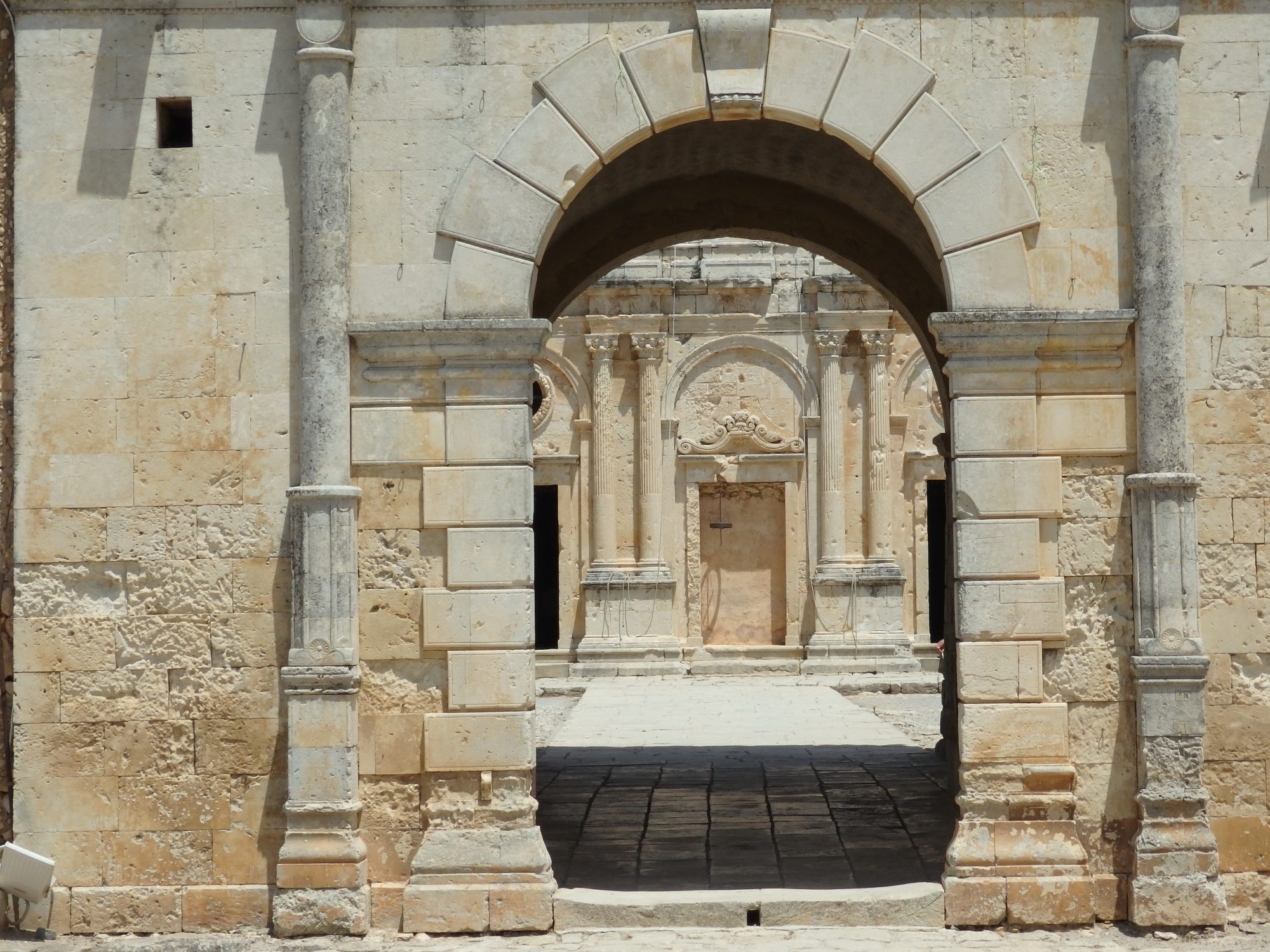 The west gate of Arkadi monastery, with the church in the background.