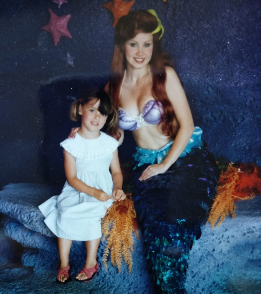 Woman dressed as Ariel: red long hair, bikini top, mermaid's tail, sitting on a stone-look bench. Next to her, a little girl wearing a light blue dress, hair in pigtails, red sandals.