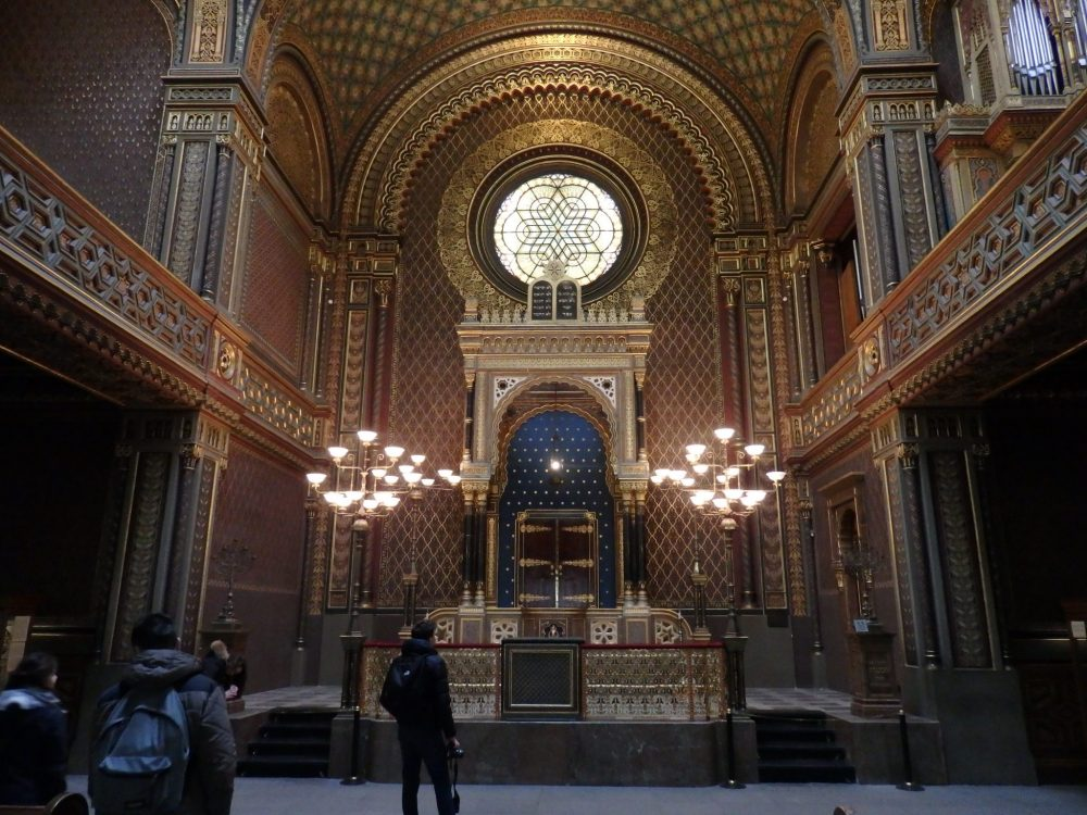 "The interior of the Spanish synagogue, one of the Prague synagogues, is very ornate with geometric patterns covering everything. Straight ahead is the torah arc, under an ornate arched structure. Above the structure is a round window with star-shaped leaded glass. The whole wall is framed in an arch as well. Along both sides of the picture the balconies of the ""women's gallery"" are visible, worked with intricate patterns of Stars of David."