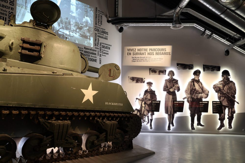 In the museum, a tank stands to the left. Beyond that a wall has images of 3 civilians (a child, a woman and a man) and a soldier.