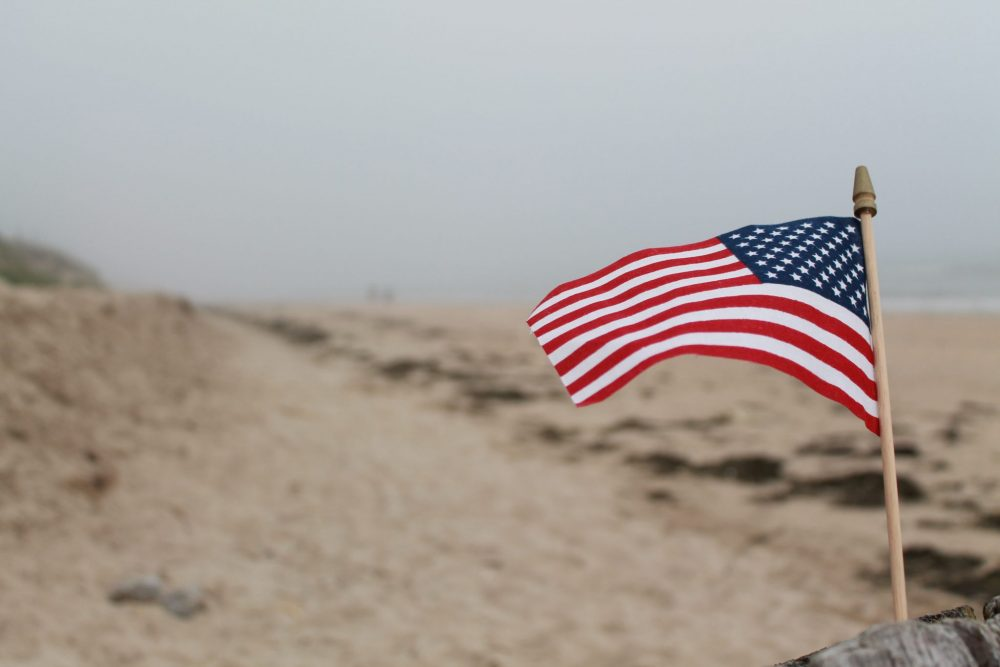 An American flag and the beach stretching behind it.