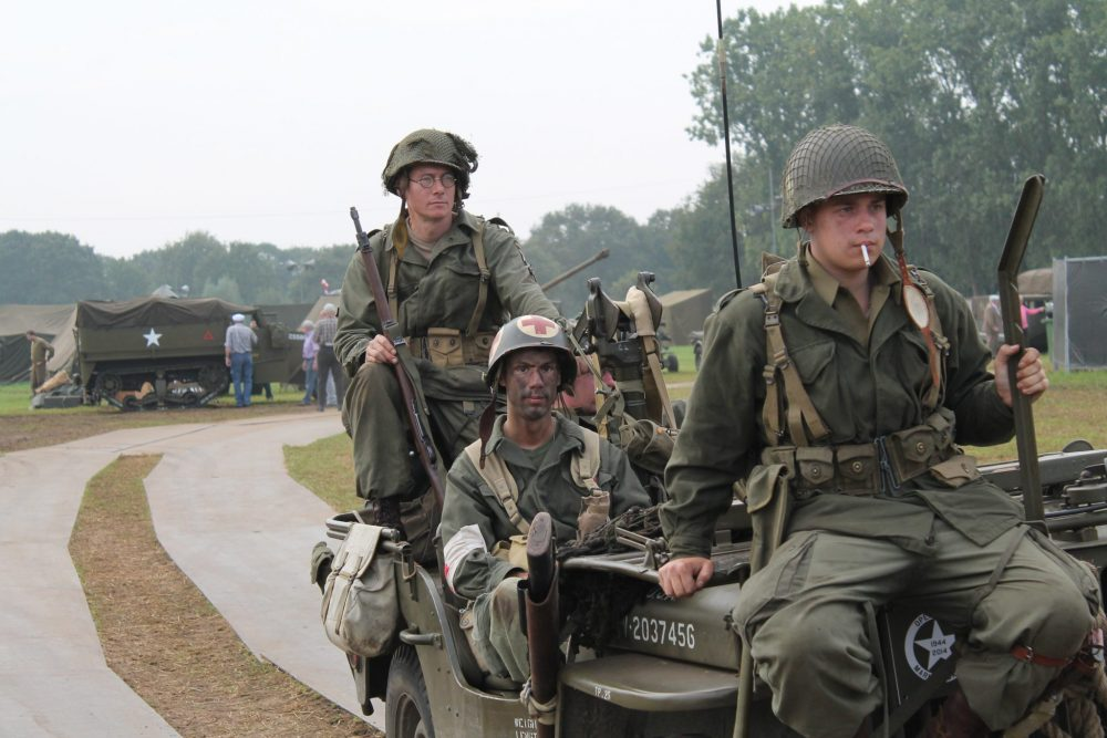 Several men in khaki camoflage uniforms, wearing helmets and holding rifles, sit on a jeep.