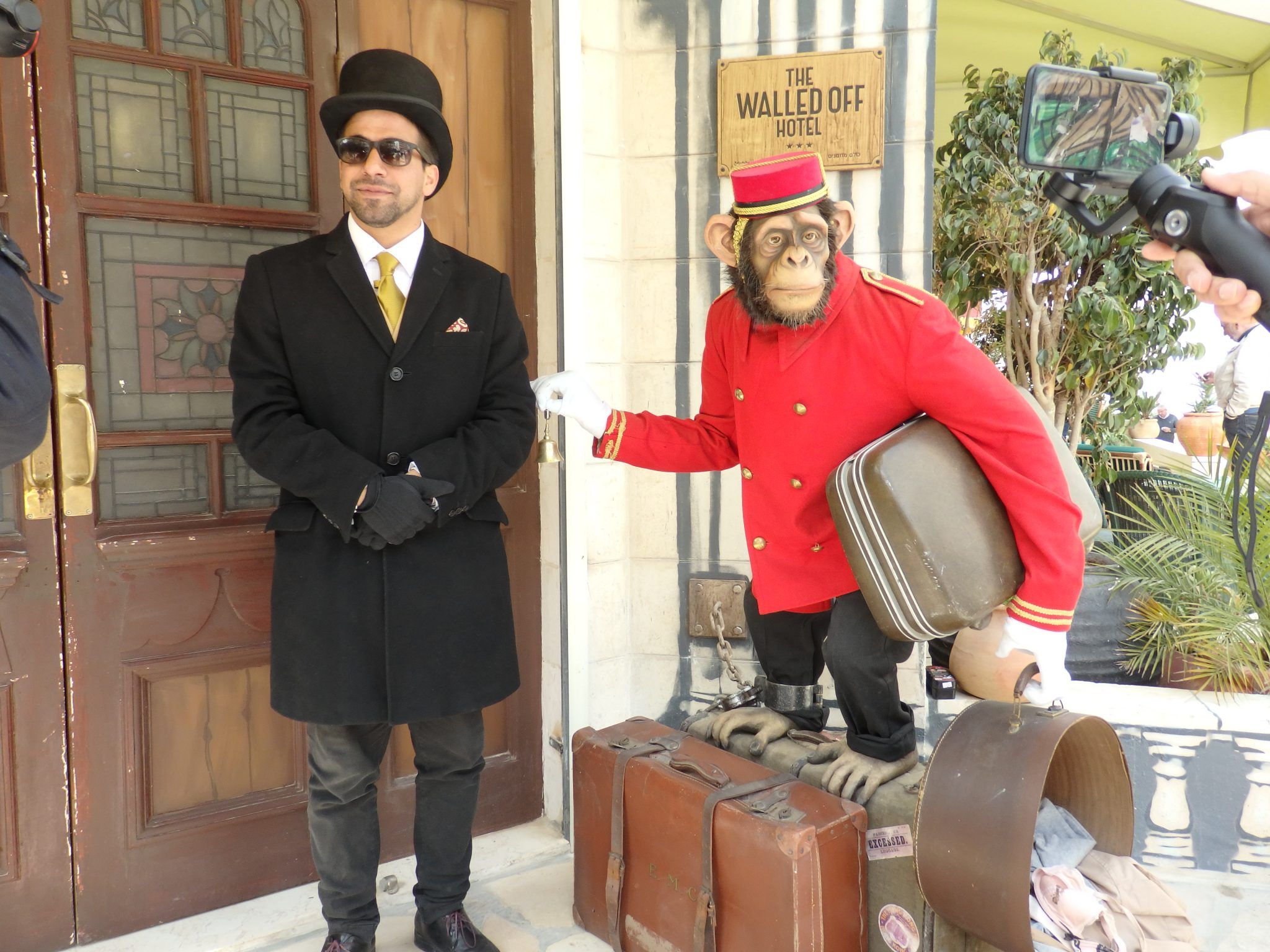 "At the entrance to the Walled Off Hotel, the doorman and the ""bellboy."" Visiting Bethlehem"