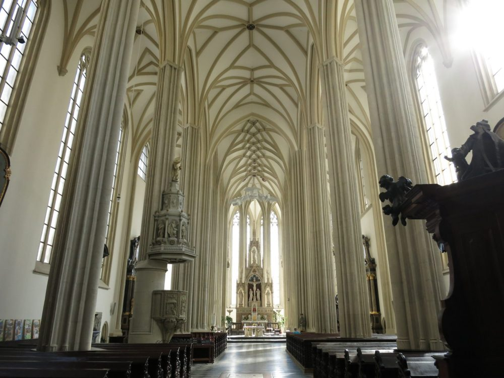 A tall central aisle with white columns on either side and gothic ceiling overhead. Far ahead is an ornate altar. Macabre sightseeing in Brno