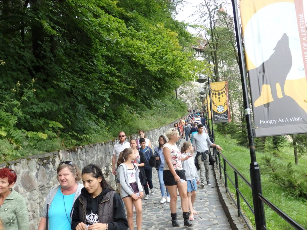 A stone path that slopes upward straight ahead toward Bran castle, only barely visible through the trees. A wall on the left with trees above it, and a railing on the right. Lots of people on the path, mostly walking toward the camera.