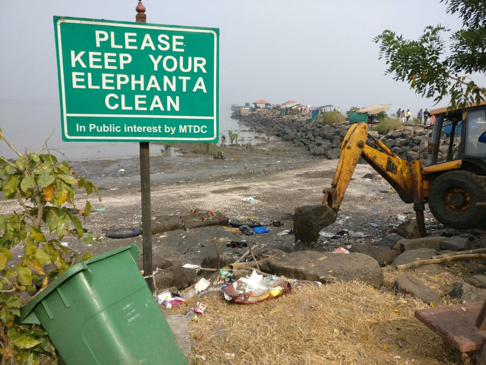 """A large sign on a pole reads """"Please keep your elephanta clean"""" and, in smaller letters underneath """"In Public interest by MTDC"""". Garbage is scattered on the ground under the sign. A green garbage bin is open and leaning against a shrub on the left. On the right is a small steamshovel. Behind this scene a beach is visible, edged by the long jetty. The beach is also strewn with trash."""