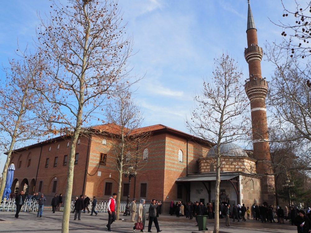 On the right of the Hacı Bayram mosque is a tall, thin minaret in red brick. A small building beside the minaret is square and single storied, except that a dome on top adds to its height. To the right of that small building, and possibly attached, is a bigger brick building, the mosque itself. It is two or three stories tall and very simple in red brick. People walk on the paved open ground in front of the buildings.