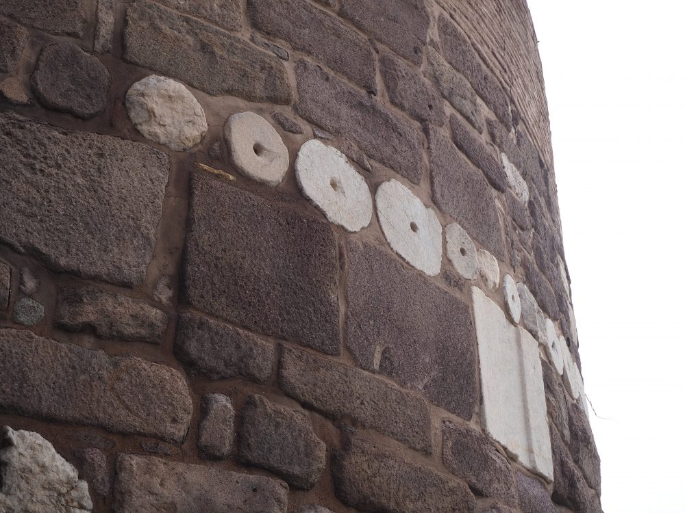 The wall is mostly a dark red, roughly-cut stone, and the whole wall curves. A row of round stones stand out in white, contrasting with the dominant dark red. The white stones are in various sizes, and look to be slices of a column. A large square slab of white is just below the row of circles.