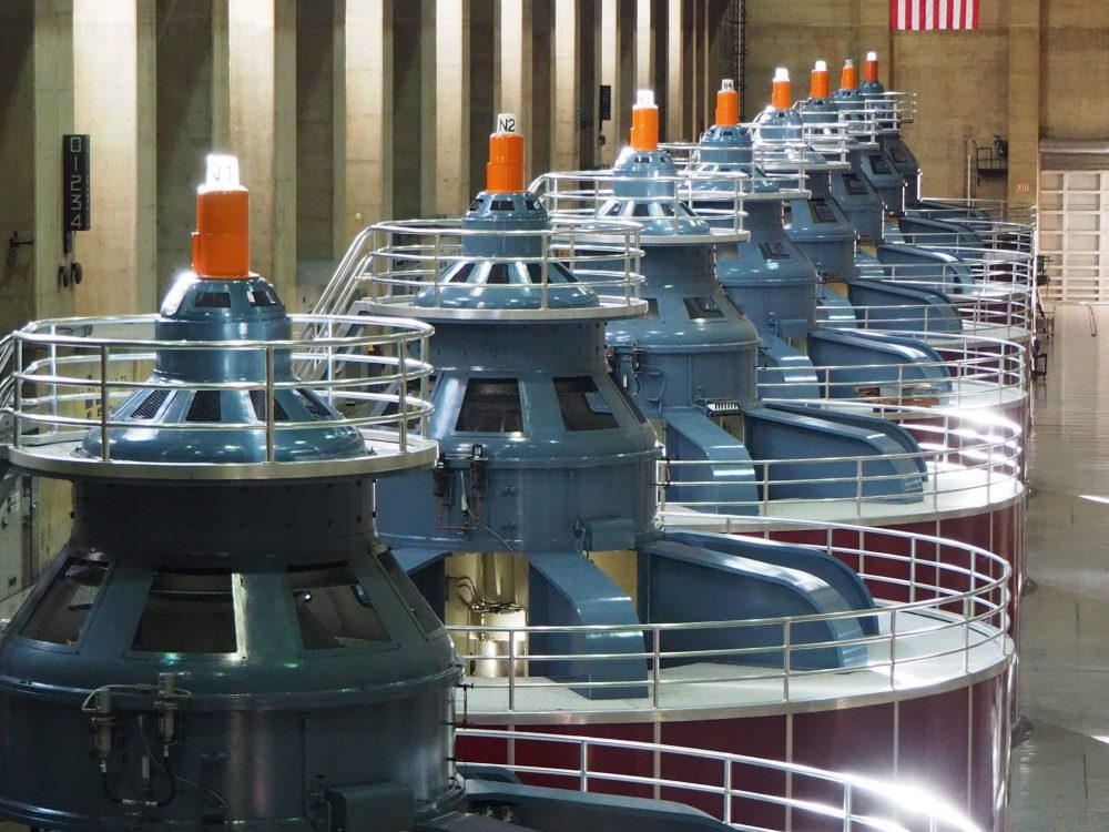 The generators are round, with a low cylinder below and a blue round thing sitting on the top of each one. I think the mechanism that turns is far below what is visible in this photo: these are just the tops of huge rotating turbines. The photo sights down a row of 7 or 8 of them.