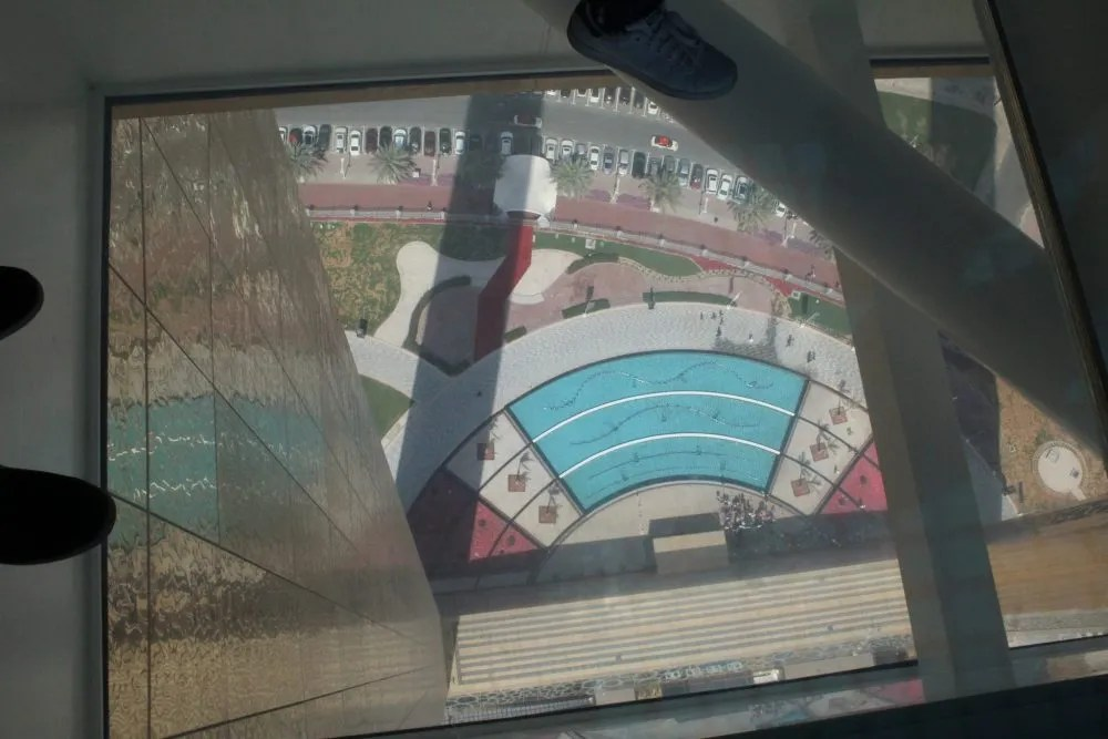 This photo, taken by my husband who has no fear of heights, looks almost straight down through one of the glass panels. You can see one of the frame's vertical sides on the left, and the fountains and flowerbeds below. If you look closely, you can make out palm trees and cars.