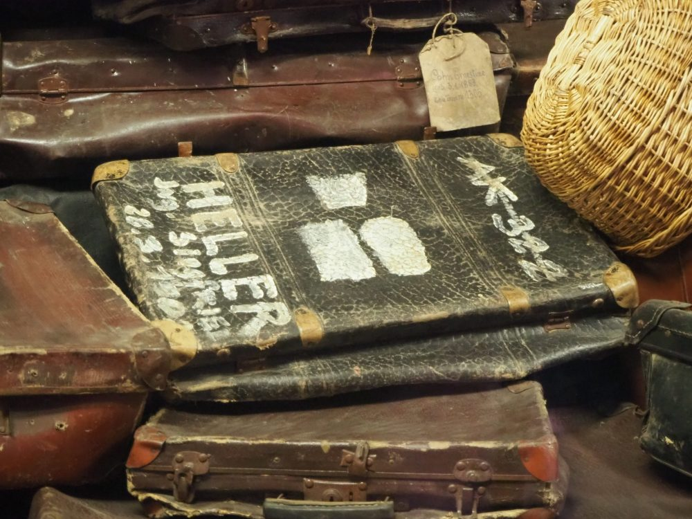 The suitcase is dark leather, well-used and dusty. The writing is in white paint. It is among many similar suitcases.