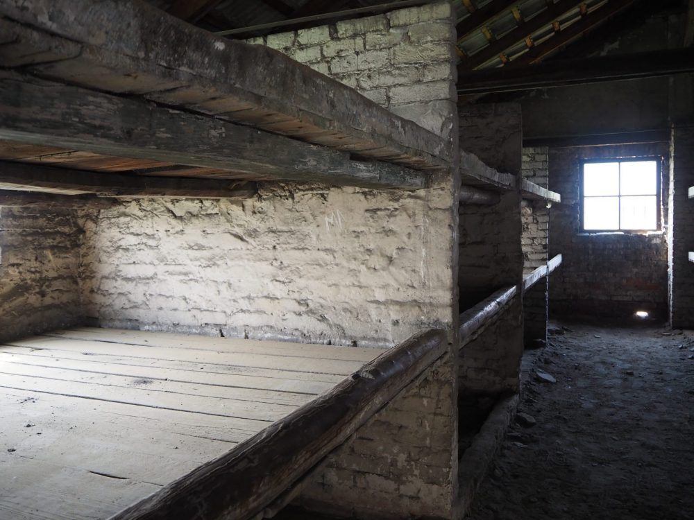 The shelves have a framework of thick wood with wooden boards laid across them. There are two shelves, and people slept on both, as well as on the floor underneath.