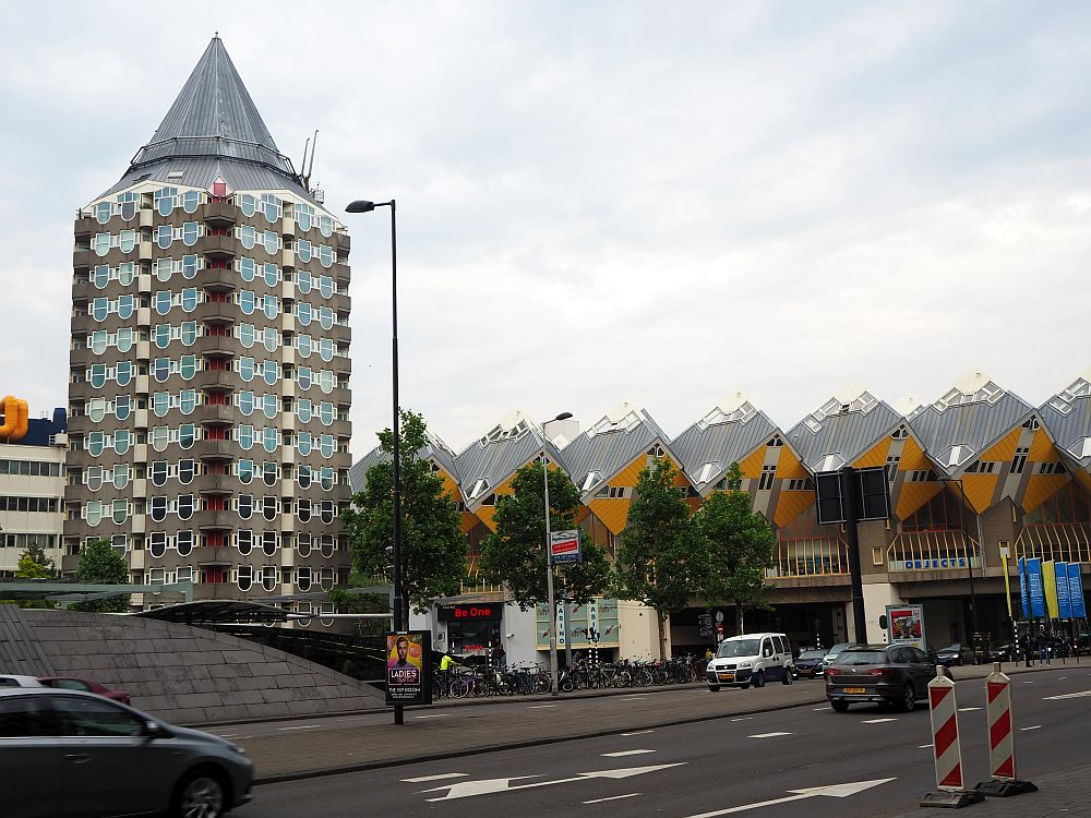 The potlood is a tall cylindrical building of about 15 stories with a round point for a roof, i.e. it's shaped like a short, fat pencil. To the right of that, the cube-shaped cube houses are visible in a row,on a sort of bridge crossing a street: yellow on one side of the cube facing down toward the street.