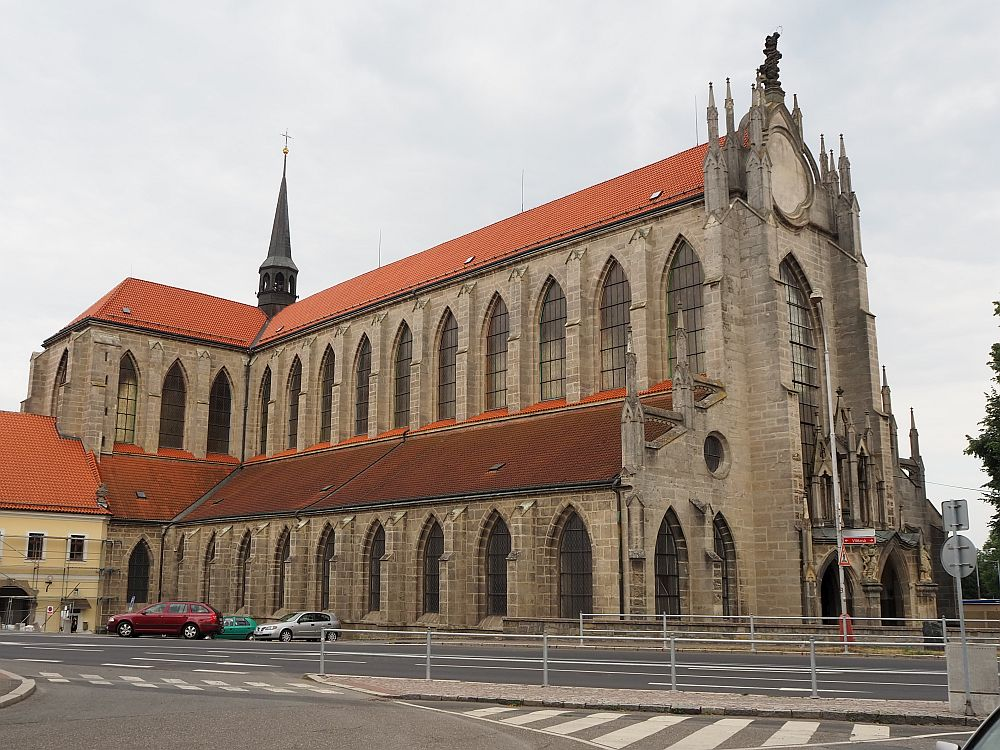 The building is lined with windows with gothic arches at the top. the lower row of about 10 windows which are smaller windows than the ones in the upper row. All in brownish stone with a red roof.