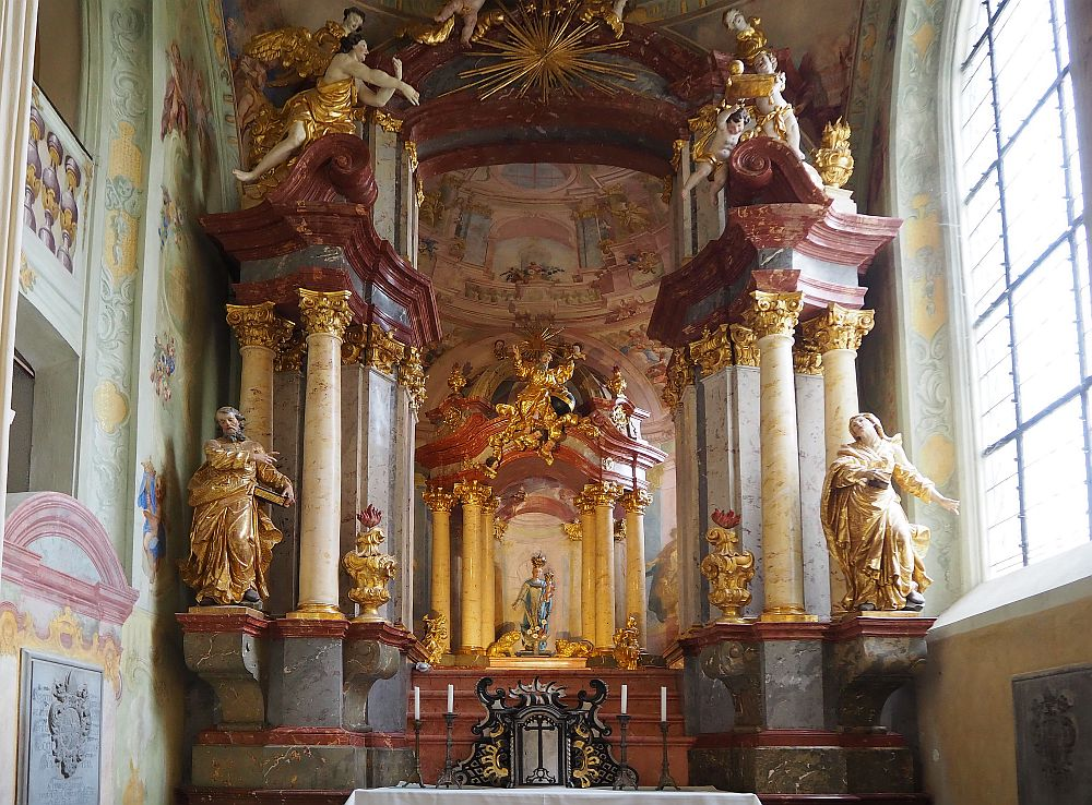 A very ornate baroque altarpiece: corinthian columns on both sides, gold-painted, with cherubs along the top and full-size angel statues on each side.